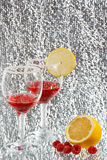 The glasses of red liquor, lemon and raspberries. The two glasses of transparent red liquor, lemon and raspberries Royalty Free Stock Images