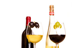 Glasses of red and white wine. Next to two bottles of wine Stock Photo