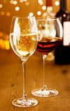 Glasses of red and white wine. Celebrating with glasses of red and white wine against a sparkling bokeh of festive party lights stock image