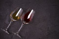 Red and white wine with cheese plate. Wine glasses with cheese, grapes, figs and nuts on black background. Glasses of red and white wine on black background stock photography