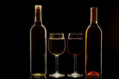 Glasses of Red and White Wine with Bottles royalty free stock photography