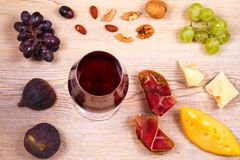 Glasses of red and white wine with cheese, prosciutto, figs and grape. Wineglass on wooden table. Wine still life. Stock Photos