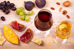 Glasses of red and white wine with cheese, prosciutto, figs and grape. Wineglass on wooden table. Wine still life. Food and drinks concept. View from above Stock Images