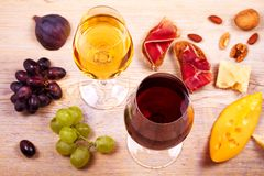 Glasses of red and white wine with cheese, prosciutto, figs and grape. Wineglass on wooden table. Wine still life. Food and drinks concept. View from above Stock Photos