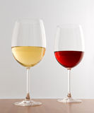 Glasses of red and white wine. Elegant glasses of red and white wine standing side by side on a wooden table against a white background royalty free stock images
