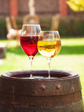 Glasses of red and white wine with grape on old wine barrel outside. Glasses of red and white wine with grape on old wine barrel outside stock image