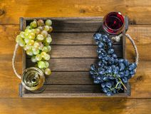 Glasses of red and white wine and grapes on a wooden background. Glasses of red and white wine and grapes in a box on a wooden background. Top view, copy-space royalty free stock image
