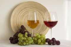 Glasses with red and white wine. With grapes brunches and wooden plate on background stock photo