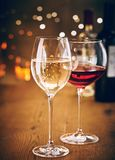 Glasses of red and white wine with party bokeh. Glasses of red and white wine on a wooden table with sparkling party lights bokeh background royalty free stock image