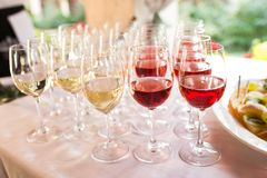 Glasses with red and white wine before party in restaurant. Beverage royalty free stock images