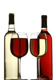 Glasses of red and white wine, with red and white wine bottles behind Stock Images