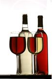 Glasses of red and white wine, with red and white wine bottles behind. Glasses of white wine and red wine standing on table with red and white wine bottles Royalty Free Stock Photo