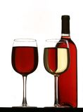 Glasses of red and white wine, with red wine bottle. Glasses of white wine and red wine standing on table, isolated on white background Stock Photography