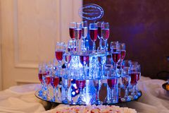 Glasses with red and white wine in the restaurant for a holiday. On a mirror surface with blue lighting stock photos