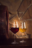 Glasses of red and white wine in wine cellar, old wine barrel. Glasses of red and white wine in wine cellar, old wine barrel stock photo