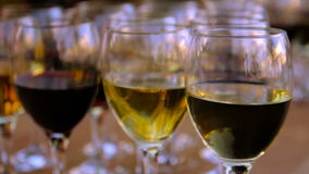 Glasses of red and white wine on a wooden table stock video footage