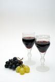 Glasses of red wine. Glasses of wine with red and green grapes stock photo