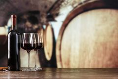 In glasses of red wine on a background of large barrels stock image