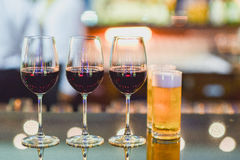 Glasses of red wine and beer on counter bar. Three glasses of wine and glass of beer on counter bar prepare foe service in night restaurant stock image