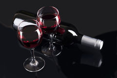Glasses with red wine and black bottle. Composition of black bottle and two glasses with red wine on the black background Royalty Free Stock Photography
