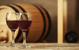 Glasses with red wine and blurred barrel. On background royalty free stock images