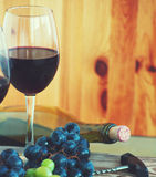 Glasses with red wine, bottle of wine, grapes and wine traffic jams. On a wooden surface Royalty Free Stock Images