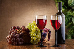 Glasses of red wine and bottle. On wooden table Stock Photography