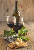 Glasses of red wine with cheese, crackers and grape Stock Images