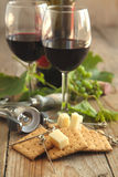 Glasses of red wine with cheese, crackers and grape Stock Photos
