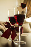Glasses of red wine with decorations burgundy bow, heart pin, greeting card. Stock Image