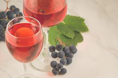 Glasses of red wine and grape/glasses of red wine and grape on a white table. Top view and copy space. Two grapes leaves marble background tasting romantic royalty free stock photos