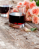Glasses of Red Wine and Pink Roses on Wooden Background Stock Image