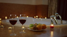 Glasses of red wine and plate with fruits standing near jacuzzi, stock video footage