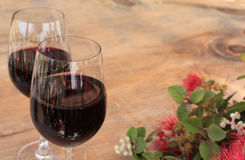 Glasses of Red Wine & Pohutukawa on Outdoor Table Royalty Free Stock Image