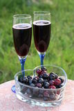 Glasses of red wine & red grapes. Two glasses of red wine in blue-stemmed glasses served outside. A heart-shaped dish with red grapes signify that wine and Stock Photo