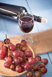 Glasses of red wine with red grapes and a bottle of wine on blue Royalty Free Stock Images