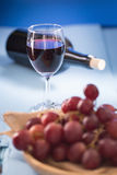 Glasses of red wine with red grapes and a bottle of wine on blue Royalty Free Stock Image