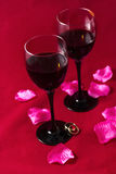 Glasses with red wine, rose petals and wedding rings on a red sh Stock Photo