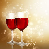 Glasses of Red Wine on Sparkling Golden Background Stock Images