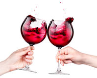 Glasses of red wine with splashes in hand isolated Royalty Free Stock Photography