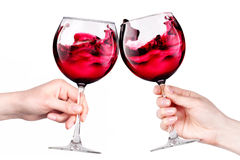 Glasses of red wine with splashes in hand isolated Royalty Free Stock Images