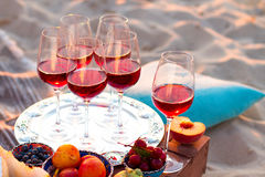Glasses of the red wine on the sunset beach Royalty Free Stock Photos