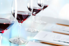 Glasses of red wine on table with pencils and paper. Royalty Free Stock Photography