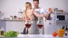Glasses of red wine on table, romantic couple dancing on background in kitchen stock footage