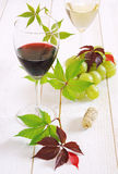 Glasses of red wine, white wine and bunch of green grapes Royalty Free Stock Image