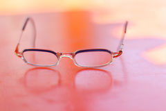 Glasses is on red woodern surface wirh reflection Stock Photos