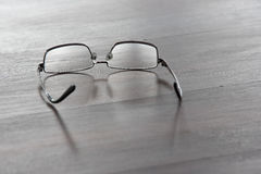 Glasses and reflection on wooden desk with shallow depth of field Royalty Free Stock Photos