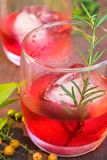 Glasses of refreshment raspberry flavor fizz with ice and rosema. Ry on wood table decorated with berry and leaf Stock Photo