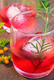 Glasses of refreshment raspberry flavor fizz with ice and rosemary. On wood table decorated with berry and leaf Royalty Free Stock Photos
