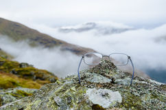 Glasses on a rock with mountain in the backgrounds Stock Images